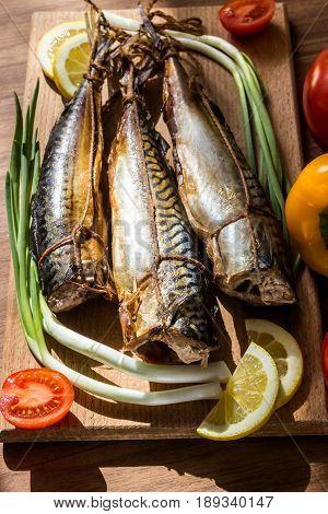 Smoked mackerel fish on wooden hardboard on wooden table