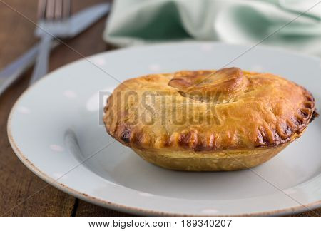 Steak meat pie with gravy - Beef pie in puff pastry close up on plate - Food background