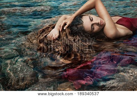 beautiful young woman in red dress laying dowm in water
