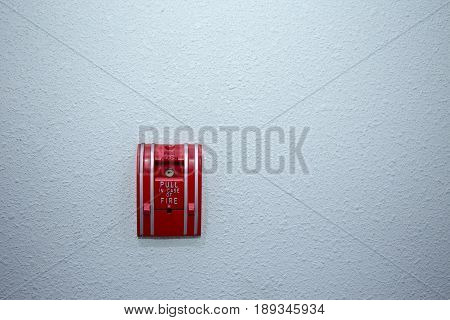 red fire alarm switch on blue wall background with copy space