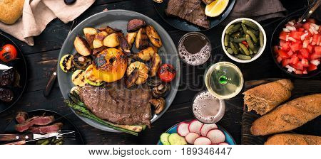 Dinner table concept. Various food cooked on the grill. Grilled steak with grilled vegetables beer and wine on a dark wooden table top view