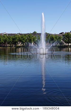 Fountain on the lake pfaffenteich in schwerin the capital city of mecklenburg-vorpommern germany blue water with reflection and blue sky with copy space