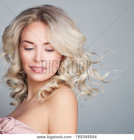 Beautiful Blonde Woman with Blowing Blonde Curly Hair. Fashion Model with Wavy Hairstyle