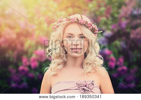 Young Blonde Woman with Flower Wreath and Sunlight Outdoors. Summer Beauty on Floral Background
