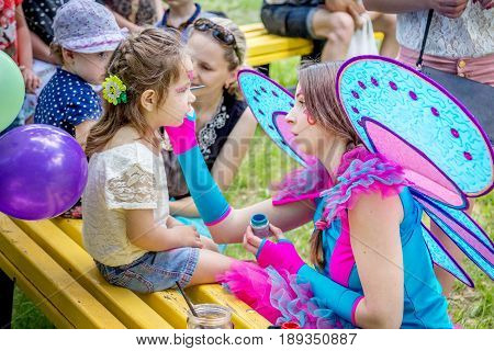 Zaporizhia/Ukraine- May 28, 2017: Charity Family festival- young woman - volunteer in colorful fairy costume, painting small  girl`s face, applying princess makeup.