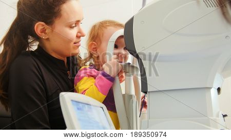Child check vision with ophthalmological apparatus at the eye clinic