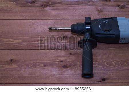 Hammer drill on a wooden background. Close-up. The electric tool.