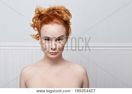 Close up of redhead young Caucasian woman with freckles wearing nothing looking at the camera with serious and concentrated expression waiting for the answer or an action from her boyfriend. Human emotions concept.