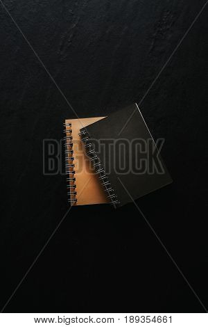 Modern note pad on black background. Top view flat lay.