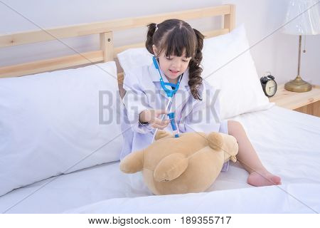 Cute Asian Little Girl Enjoy Playing Doctor With Doctor Toy Set And Cute Doll At Home.photo Design F