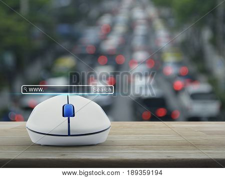 Search www button with wireless computer mouse on wooden table over blur of rush hour with cars and road Searching system and internet concept