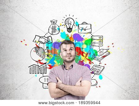 Pensive bearded young man standing near a concrete wall looking upwards. There is a colorful time management sketch