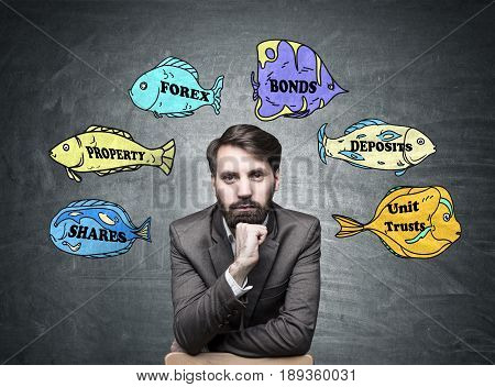 Portrait of a confident bearded businessman wearing a brown suit and sitting near a blackboard with business buzzwords written on fish of different colors.
