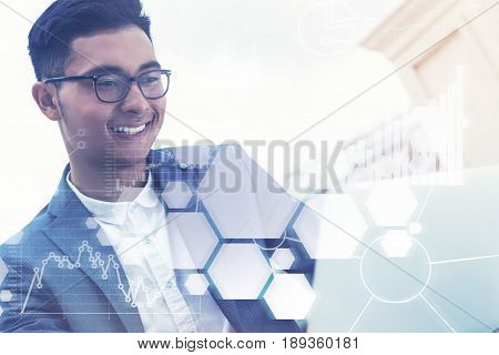 Young Asian businessman sitting at his workplace and portraying success in business and good social skills. Toned image double exposure.