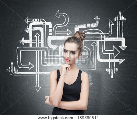 Portrait of a beautiful and pensive young woman wearing a black tank top. Her hair is in a bun. She is thinking and half smiling. Blackboard background with a tangled arrows sketch.