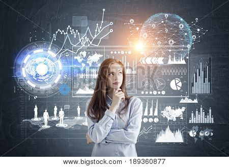 Portrait of a pensive young business analyst standing against a dark background with graphs and infographics. Toned image.