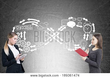 Side view of two serious businesswomen one of which is reading a book while her colleague is taking notes are standing near a blackboard with infinity business sketch. Concept of never ending routine