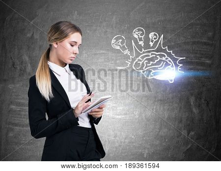 Side view of a strict blond businesswoman standing with a notebook and a pen near a blackboard with a brain sketch. There are light bulbs above it. Toned image