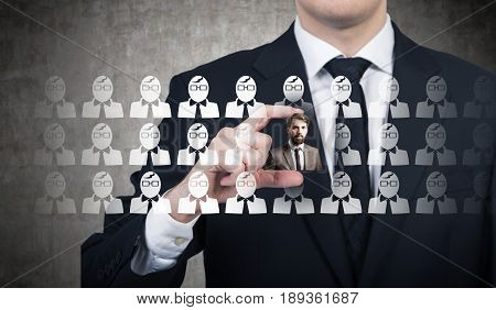 Close up of an unrecognizable young businessman in a suit with a black tie picking up the right candidate for a vacant position in his company. Blackboard. Concept of recruitment.