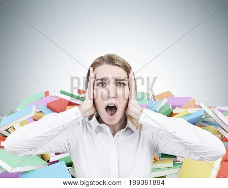 Close up of a blond businesswoman wearing a white shirt and screaming in terror. There are piles of book of different color behind her. Mock up