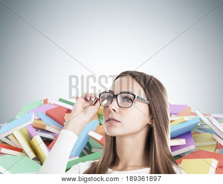 Close up of a young blond woman wearing glasses. She is standing near a gray wall with piles of book lying around. Concept of a book worm. Mock up