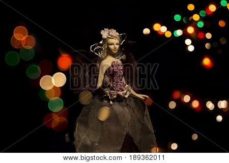 Porcelain Fairy With Wings On A Bokeh Lights Background.