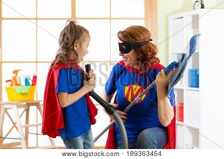 Happy woman and kid cleaning room and have a fun. Mother and her child girl playing together. Family in Superhero costumes.