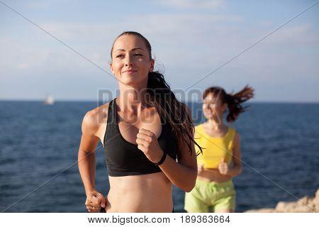 girls play sports running around on the Ocean Beach