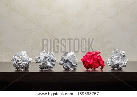 Five crumpled paper balls on a dark wooden table. Research or creative process concept