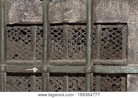 an old window with iron bars and fine mesh, covered with a century old dust , close-up
