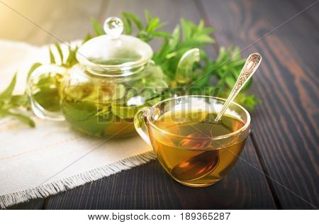 Cup of mint tea and a bunch of mint on the table. Glass teapot with green tea.