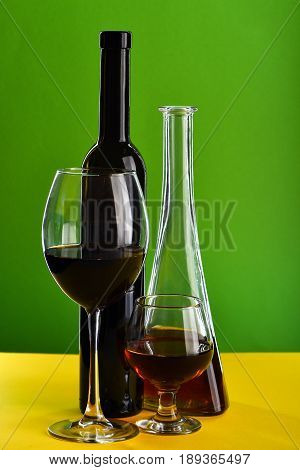 Glasses With Different Beverages Near Bottles