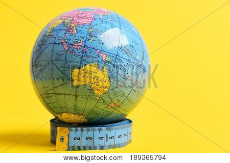 Globe model standing on roll of blue measuring tape isolated on yellow background with copy space. Visible hemisphere which contains Australia on it