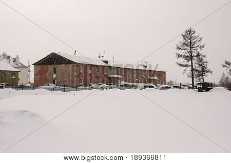 New Urengoy, YaNAO, North of Russia. February 02, 2013. Old two-storied  red house in winter with snow, cars and trees on the yard. Poverty and misery, North
