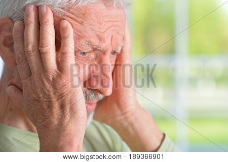 Old sad man at home on the window background