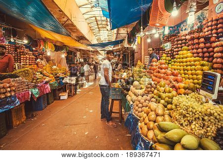 MYSORE, INDIA - FEB 16, 2017: Traders of exotic tropical fruits made colorful showcases on city market on February 16, 2017. With population 900000 Mysore is the cultural capital of Karnataka