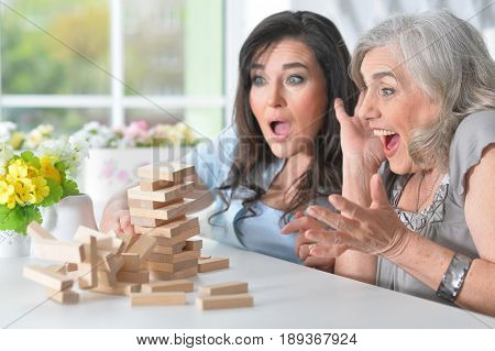 Old people play a board game at the table at home