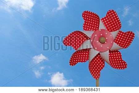 red and white pinwheel against blue sky