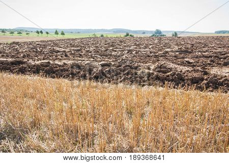 Plowed field with big clods besides a stubble-field