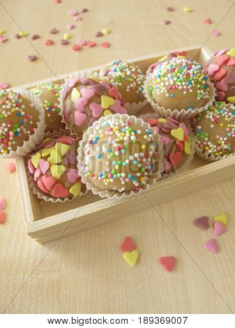 Homemade marzipan sweets with sugar hearts and pearls in wooden box