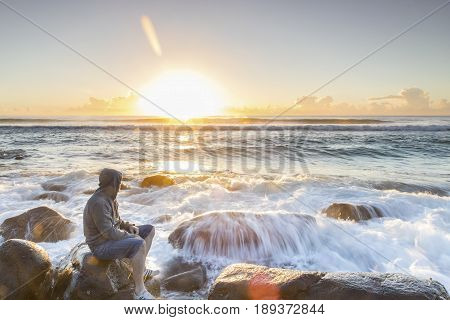 GOLD COAST, AUSTRALIA - MAY 28 2017: Person sitting on a rock watching the sunrise over the ocean, with ocean tide cascading over a rock. Burleigh Heads Gold Coast