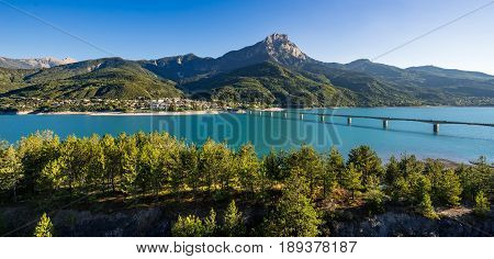 Summer panoramic view of Serre-Poncon Lake with Savines-le-Lac its bridge and the Grand Morgon mountain peak. Hautes-Alpes PACA Region Southern French Alps France