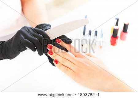 Beauty salon hand care. Studio photography. The process of caring for the hands. Nails filing with file.