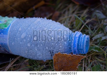 bottle of Water in ice lay on the ground