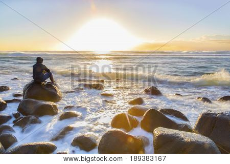 GOLD COAST, AUSTRALIA - JUNE 3 2017: Person sitting on a rock watching the sunrise over the ocean, with ocean tide coming in over the rocks. Burleigh Heads Gold Coast