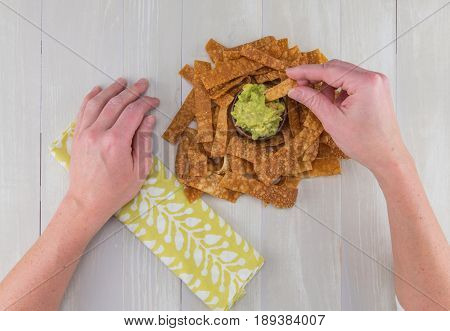 Right Hand Reaches Out To Dip Chip In Guacamole