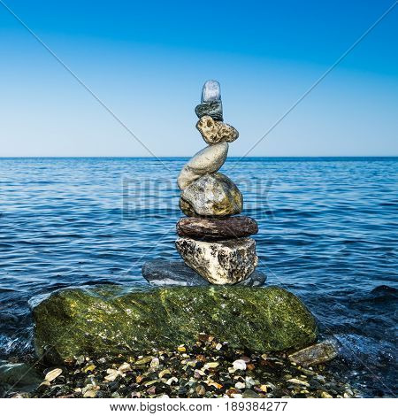 Colorful zen balancing rocks with blue sea background