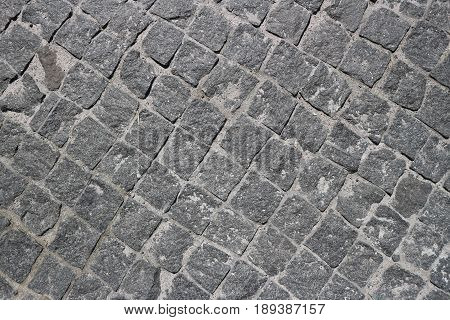 Rubble gray square stones paved road with a diagonal rotation.