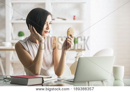 Woman At Workplace Looking In Small Mirror