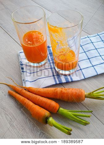Glasses Of Carrot Juice And Fresh Carrots On Wooden Cutting Board, Knocked The Juice, The Empty Glas